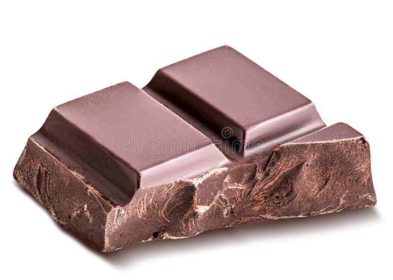 El pedazo de chocolate negro se aísla en un fondo blanco fotografía de archivo