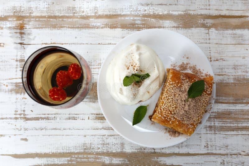 El pedazo de empanada tradicional del milhojas de manzana sirvió con helado, la menta fresca, la frambuesa y el vidrio de vino imagen de archivo libre de regalías
