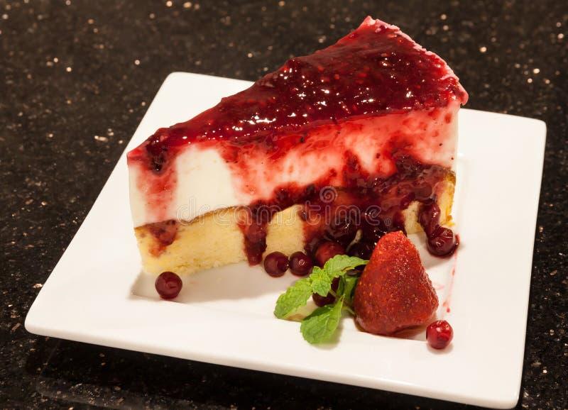 El pedazo de pastel de queso con las bayas mezcladas sauce servido en s blanco imágenes de archivo libres de regalías