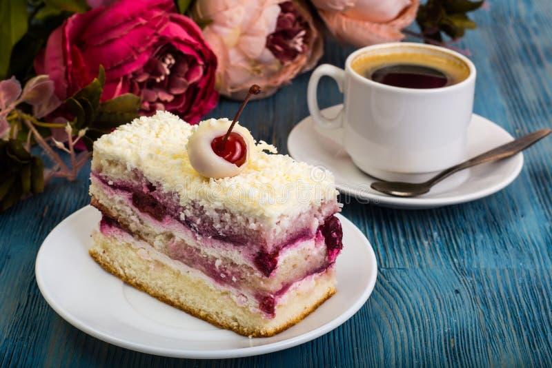 El pedazo de torta, bizcochos esponjosos, crema, cerezas, azotó la crema en b fotos de archivo libres de regalías