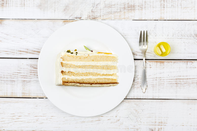 El pedazo de torta sirvió en los cubiertos y las píldoras de la placa que regulaban el azúcar de sangre al lado de él imagen de archivo