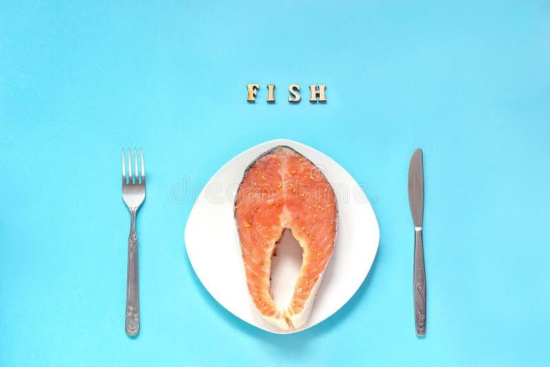El pedazo del filete de rojo adobó pescados en la placa, el cuchillo y la bifurcación blancos imagen de archivo