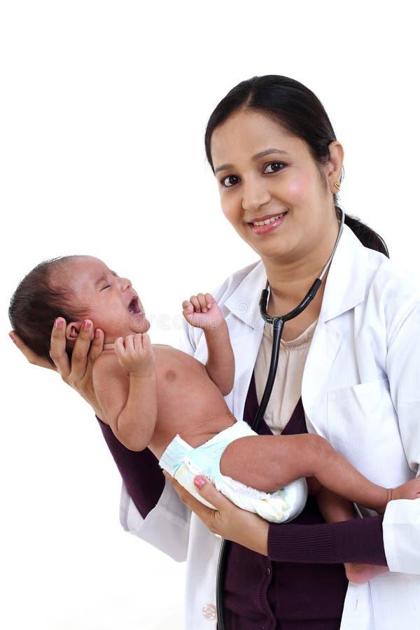 El pediatra de sexo femenino detiene al bebé recién nacido imagen de archivo