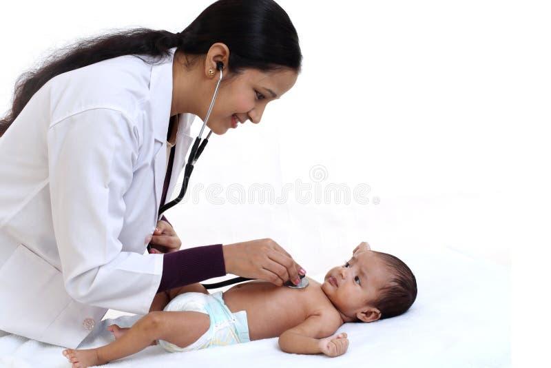 El pediatra de sexo femenino detiene al bebé recién nacido foto de archivo libre de regalías
