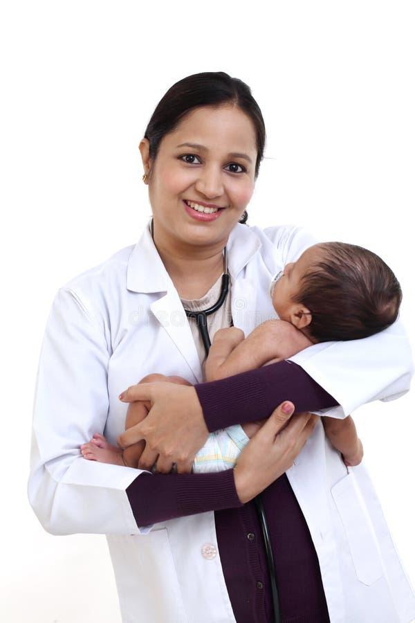 El pediatra de sexo femenino detiene al bebé recién nacido foto de archivo