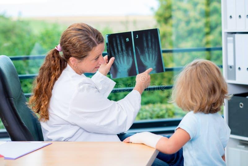 El pediatra de sexo femenino en la capa blanca del laboratorio examinó al pequeño paciente fotos de archivo libres de regalías