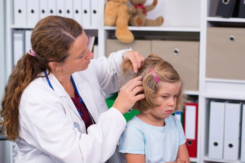 El pediatra de sexo femenino en la capa blanca del laboratorio examinó al pequeño paciente imagen de archivo