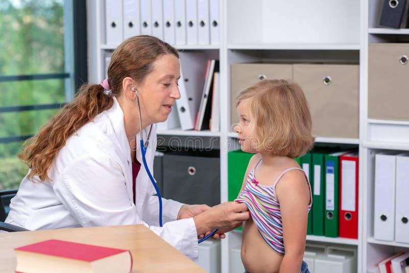 El pediatra de sexo femenino en la capa blanca del laboratorio examin? al peque?o paciente imagen de archivo