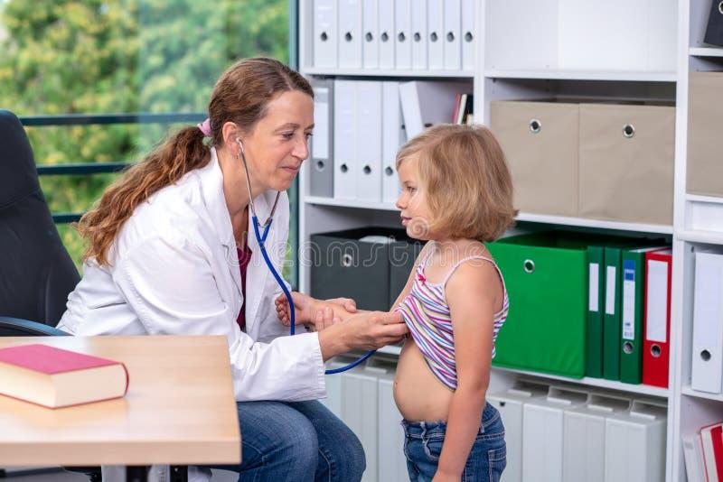 El pediatra de sexo femenino en la capa blanca del laboratorio examin? al peque?o paciente fotos de archivo
