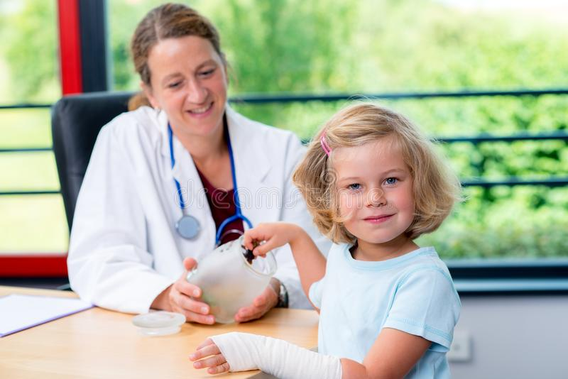 El pediatra de sexo femenino tiene candys para una niña foto de archivo