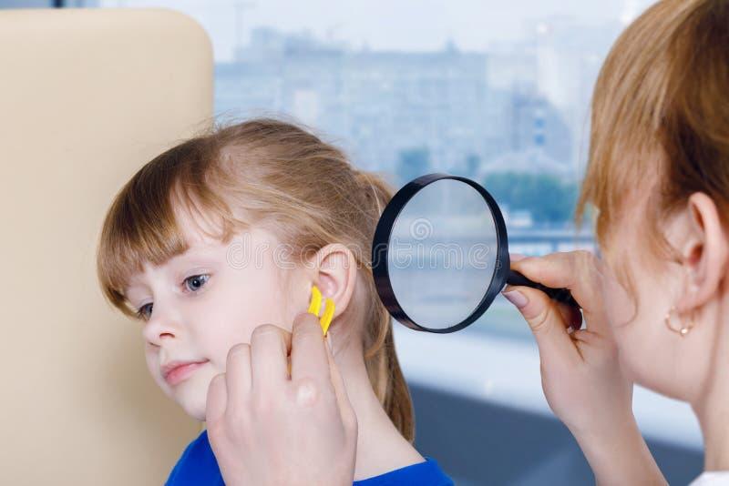 El pediatra está comprobando un oído de un pequeño niño mientras que la trata fotografía de archivo
