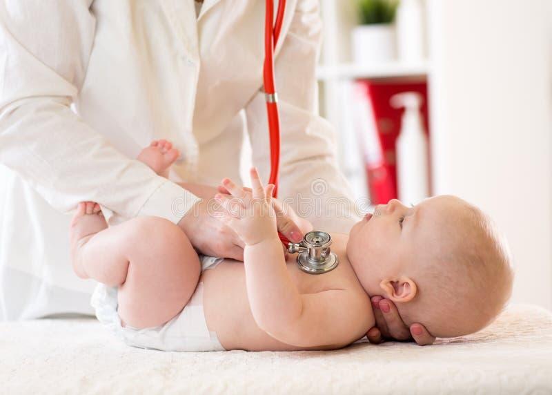 El pediatra examina cinco meses de bebé Doctor que usa el estetoscopio para escuchar el pecho del niño que comprueba golpe de cor imagen de archivo libre de regalías