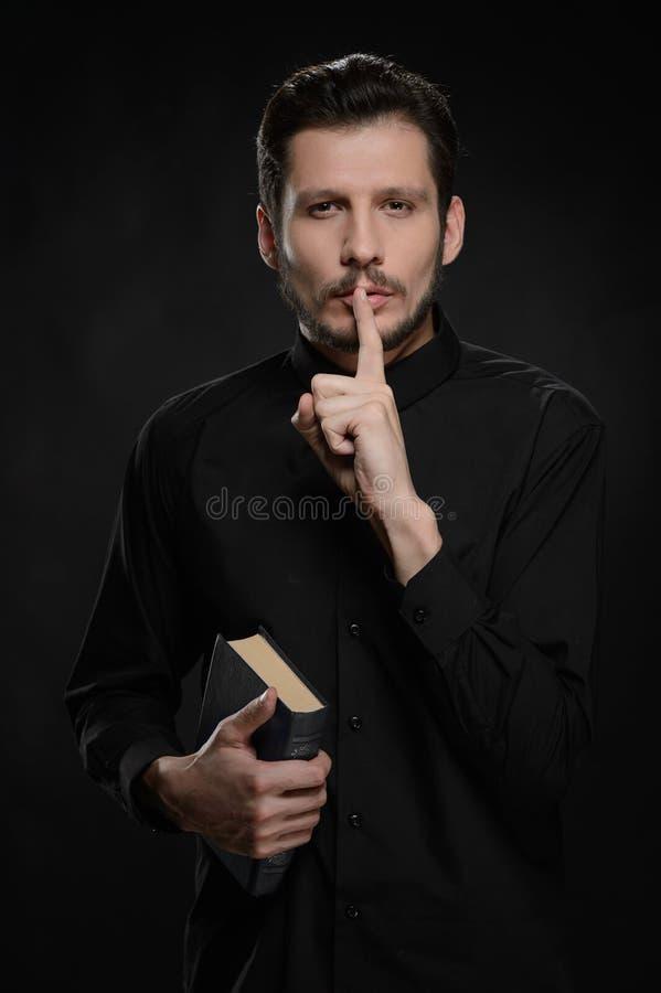 El pedir guardar silencio. Retrato del sacerdote que sostiene su agai de la mano fotos de archivo libres de regalías