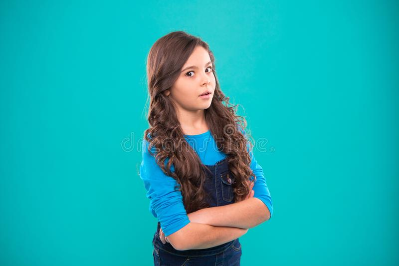El peinado rizado de la muchacha se siente confiado Las manos del control del niño cruzaron con confianza la psicología infantil  imagen de archivo libre de regalías