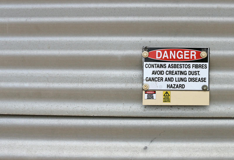 El peligro, contiene la señal de peligro del amianto foto de archivo
