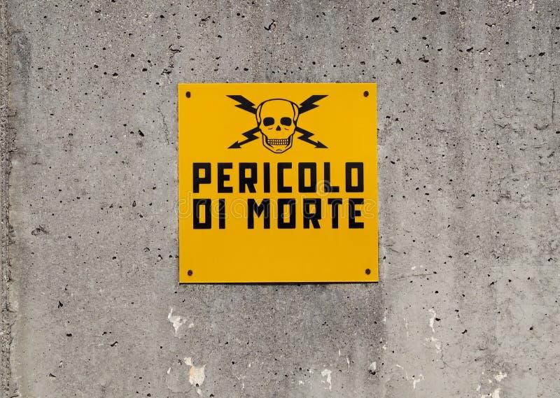 El peligro de la muestra de la muerte, en de lengua italiana, representada por un cráneo con dos cruzó el relámpago en un muro de fotografía de archivo libre de regalías
