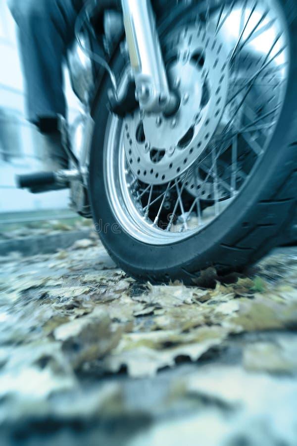 El peligro de montar una motocicleta en las hojas mojadas fotografía de archivo libre de regalías
