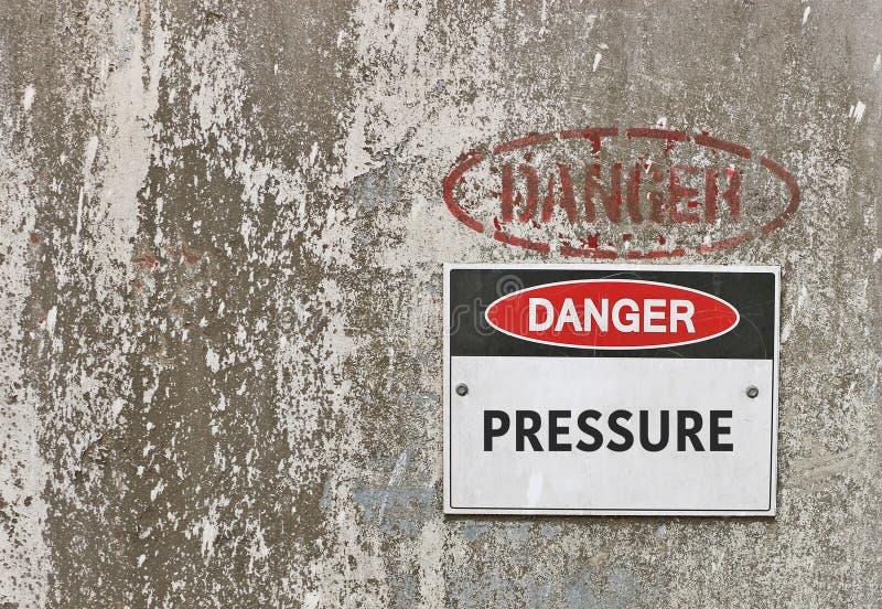 El peligro rojo, blanco y negro, ejerce presión sobre la señal de peligro fotografía de archivo