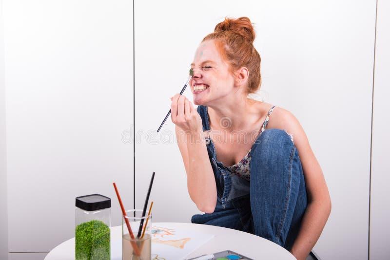 El pelirrojo atractivo se está riendo durante la pintura con colo del agua imagen de archivo