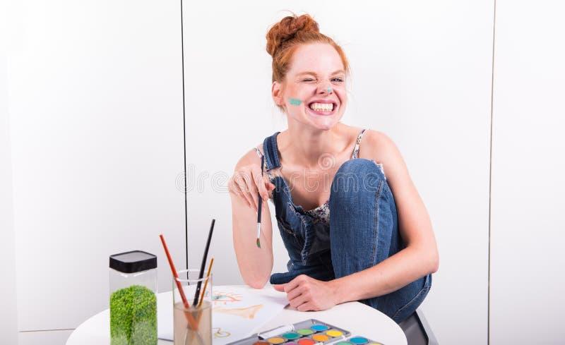 El pelirrojo atractivo se está riendo durante la pintura con colo del agua foto de archivo libre de regalías