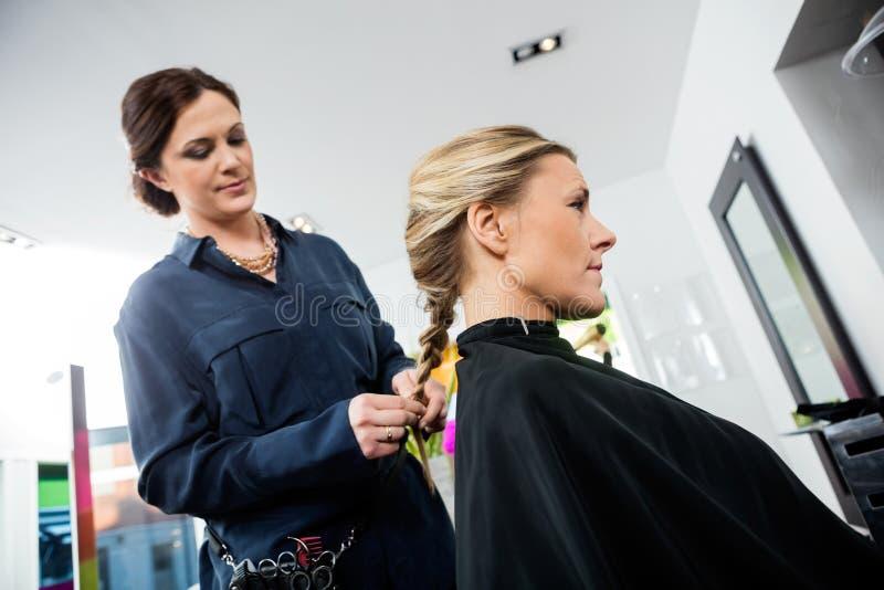 El pelo de Braiding Client femenino del peluquero imagen de archivo