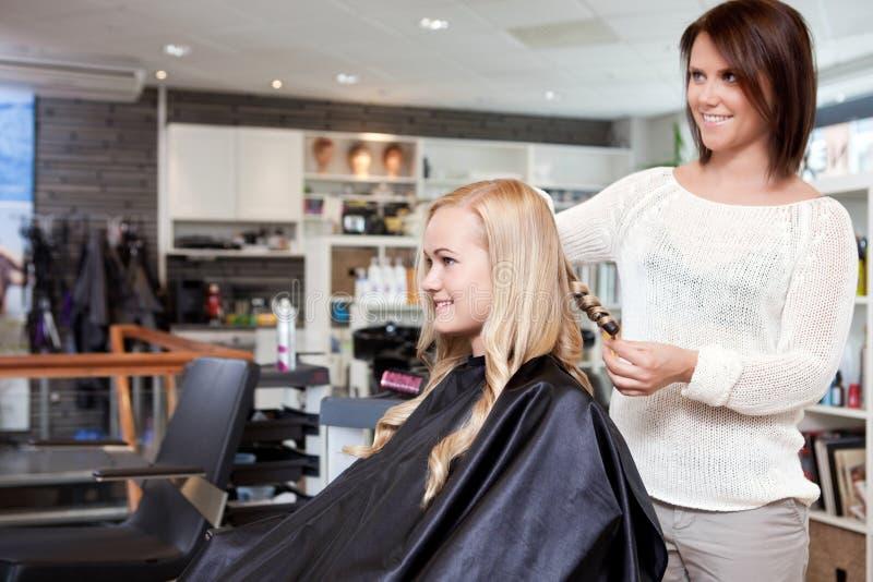 El pelo de Curling Customer del peluquero imágenes de archivo libres de regalías