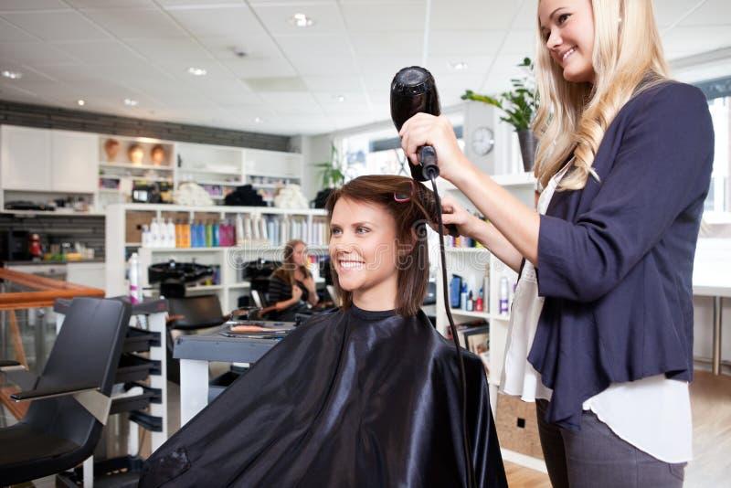 El pelo de Drying Customer del peluquero imágenes de archivo libres de regalías