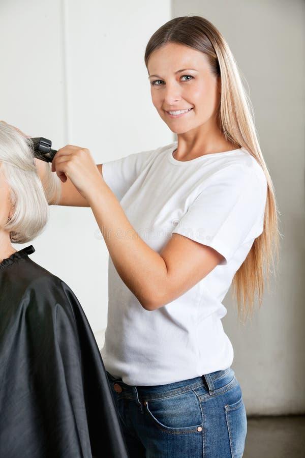 El pelo de Ironing Female Client del peluquero foto de archivo
