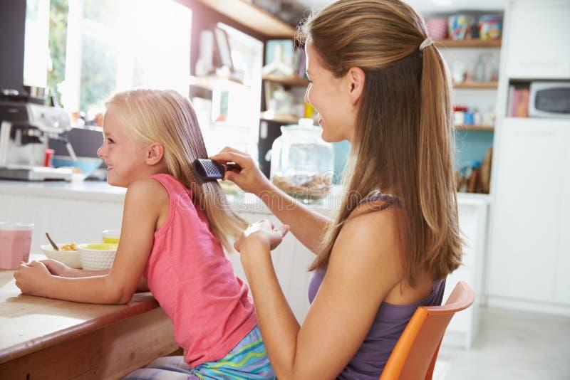 El pelo de la hija de cepillado de la madre en la mesa de desayuno imagen de archivo