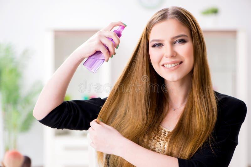 El pelo de rociadura de la mujer joven pule a su pelo imagenes de archivo