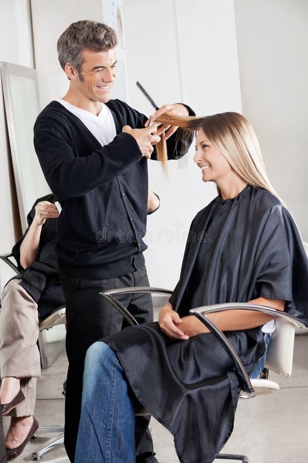 El pelo del cliente del corte del peluquero en sala imagen de archivo