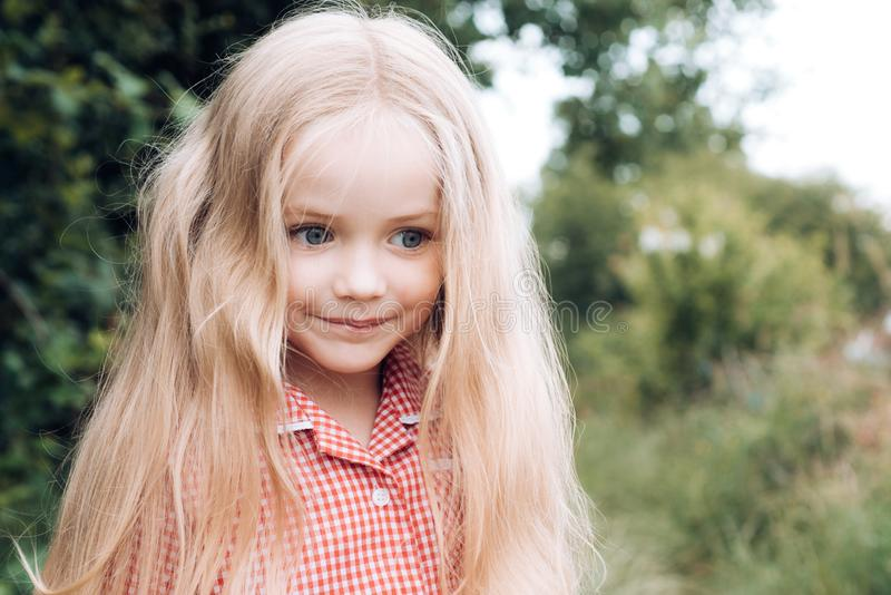 El pelo es parte parte importante de su mirada Pequeña muchacha con el pelo rubio Pequeño niño feliz con sonrisa adorable Pequeño fotografía de archivo