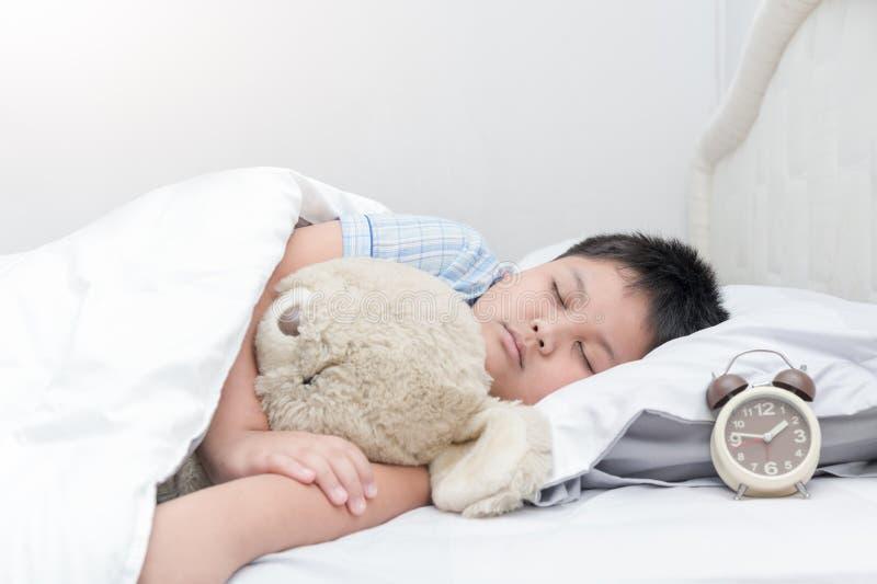 El peluche gordo obeso del sueño y del abrazo del muchacho refiere la cama, fotos de archivo libres de regalías