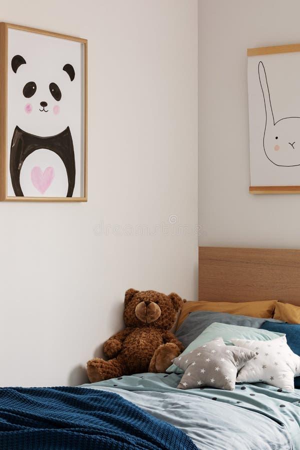 El peluche refiere la sola cama de madera en interior azul y anaranjado del dormitorio fotografía de archivo libre de regalías