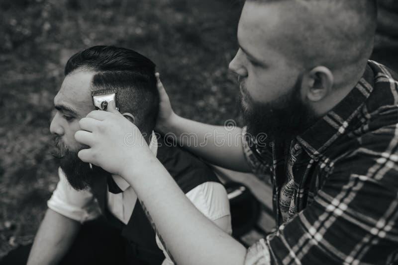 El peluquero afeita a un hombre barbudo foto de archivo libre de regalías