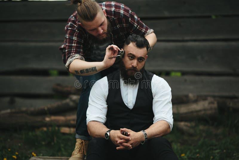 El peluquero afeita a un hombre barbudo fotos de archivo libres de regalías
