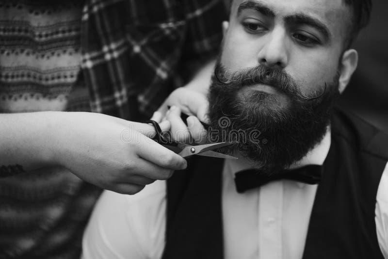 El peluquero afeita a un hombre barbudo imagenes de archivo