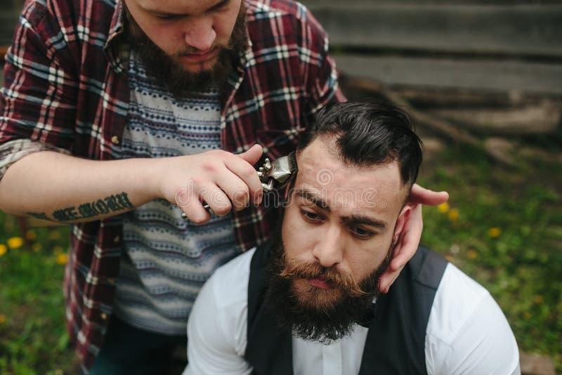 El peluquero afeita a un hombre barbudo imagen de archivo