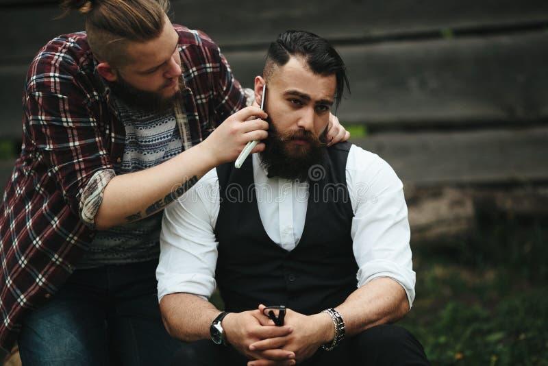 El peluquero afeita a un hombre barbudo fotografía de archivo