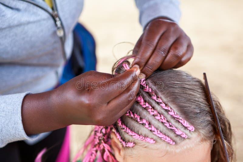 El peluquero afroamericano da dreadlocks rosados hechos en el estilo africano para la muchacha europea joven imagenes de archivo