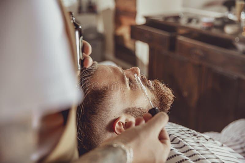 El peluquero aplica el aceite de la barba con un dropper fotos de archivo libres de regalías