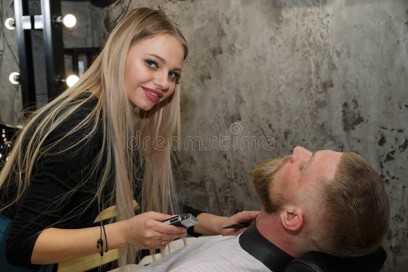 El peluquero corta la barba del cliente en la peluquería fotos de archivo