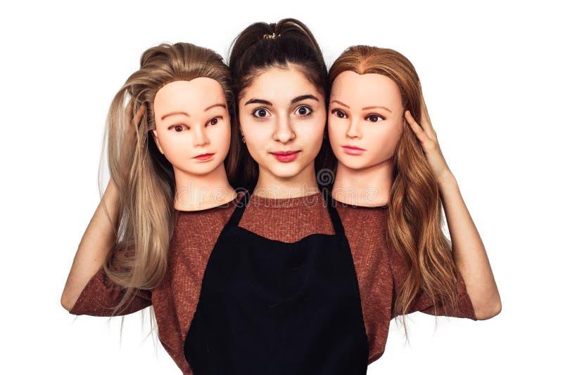 El peluquero de la chica joven lleva a cabo en manos dos cabezas del maniquí Mujer con tres cabezas fotos de archivo libres de regalías