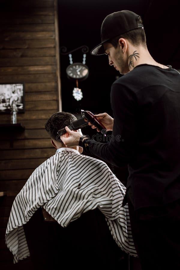 El peluquero de la moda hace un pelo del corte de maquinilla de afeitar para un hombre negro-cabelludo elegante en una barbería e fotos de archivo