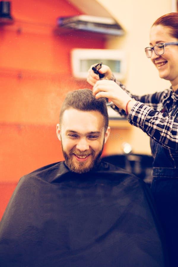 El peluquero de sexo femenino está cortando el pelo del cliente sonriente barbudo del hombre imagenes de archivo