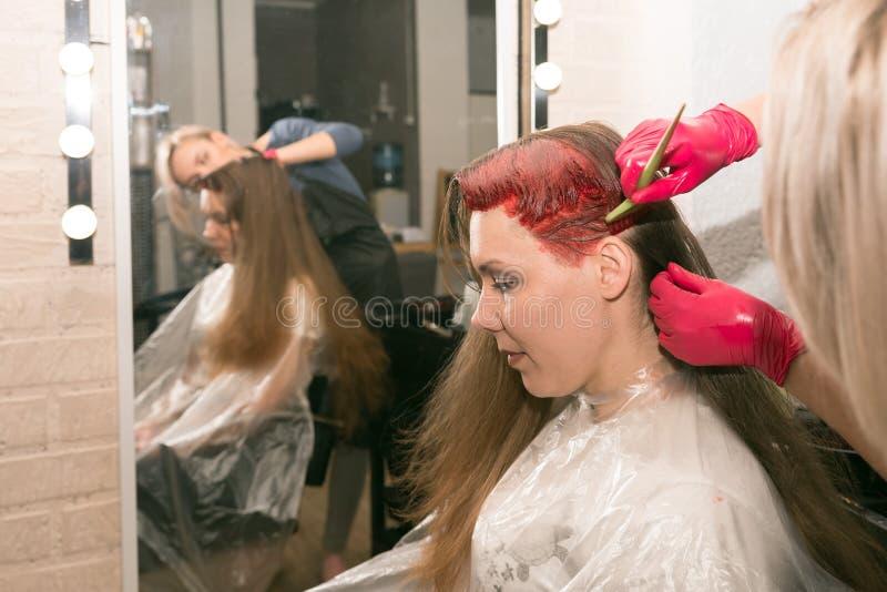 El peluquero de sexo femenino pinta un pelo de los girl's con un cepillo, delante de un espejo en el salón de los hairdresser†imagen de archivo