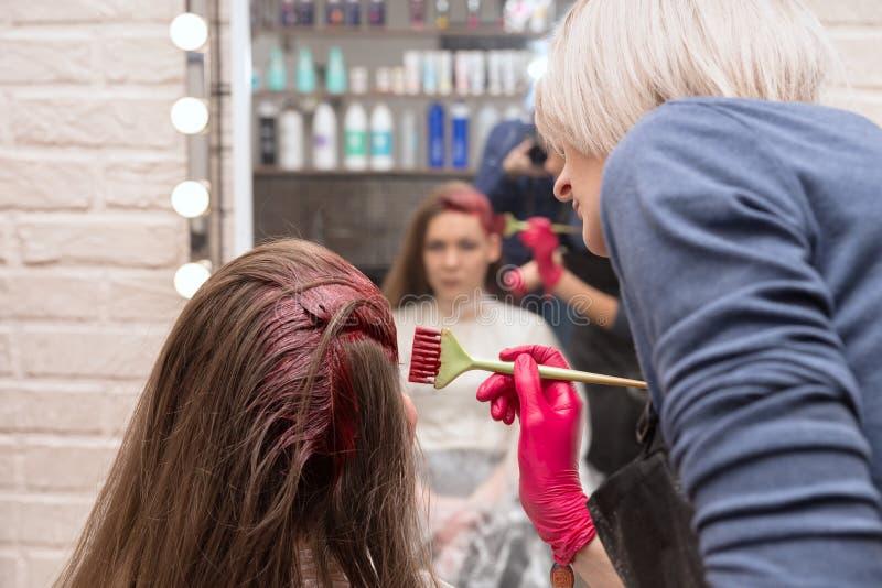 El peluquero de sexo femenino pinta un pelo de los girl's con un cepillo, delante de un espejo imagenes de archivo