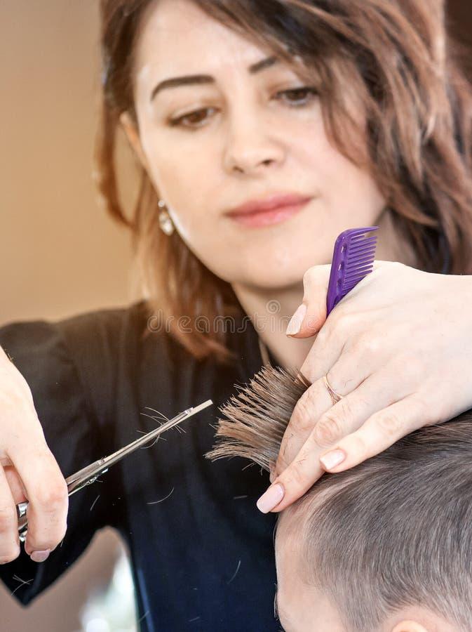 El peluquero del peluquero corta al hombre joven en un sal?n de belleza opinión al peluquero con luz del sol imagenes de archivo
