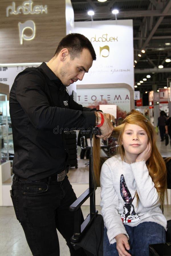El peluquero del estilista hace dise?ar a una chica joven foto de archivo