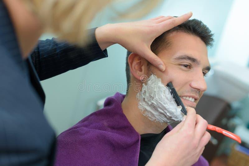 El peluquero del hombre afeita la barba de los clientes foto de archivo